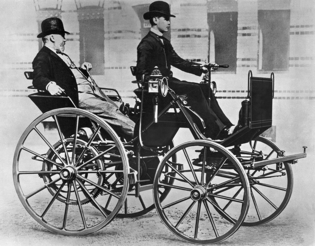 Gottlieb Daimler sitter komfortabelt i baksetet, mens sønnen Adolf kjører motorvognen.
