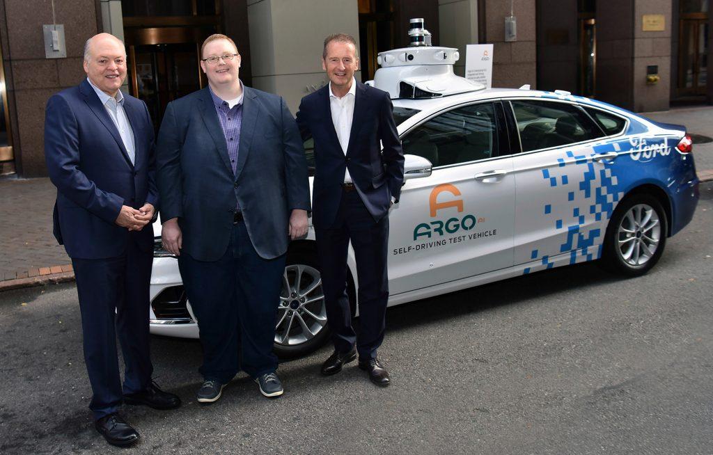 VW-sjef Herbert Diess (t.v.) og Ford-president Jim Hackett (t.h.) har kjøpt seg inn i Argo Ai, her med den smilende direktøren Bryan Salesky i midten. (Foto: VW)